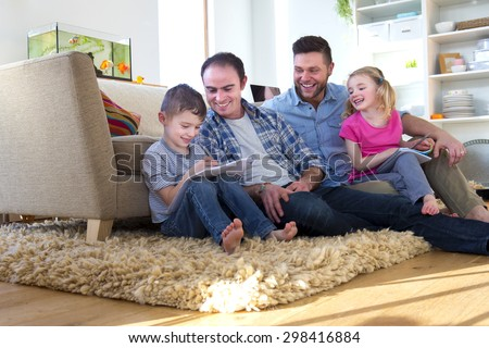 male couple sitting on the floor of their front room with their children, helping them do their homework - stock photo