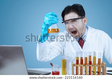 Male crazy asian scientist doing research with laptop computer and chemistry fluid - stock photo