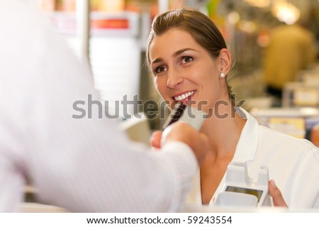 Male customer in supermarket handing his credit card to cashier at the checkout desk in order to pay - stock photo