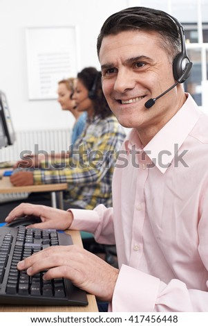 Male Customer Services Agent In Call Centre - stock photo