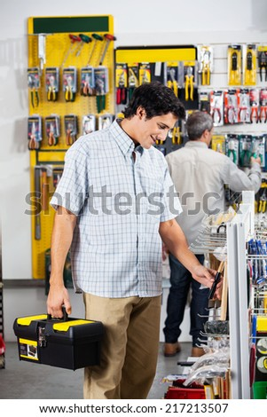 Male customers buying tools in hardware store