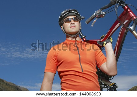 Male cyclist carrying bike against blue sky - stock photo