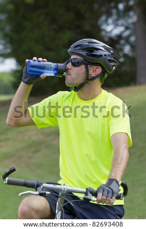 Male cyclist preparing to ride a mountain bike in a park - stock photo