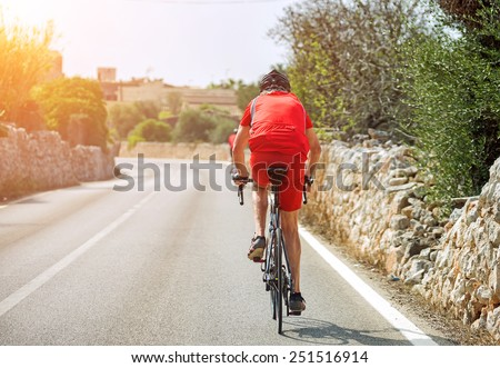 Male cyclist riding a bicycle on the road. - stock photo