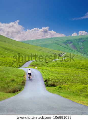 male cyclist riding up a hill on a road in summer portrait - stock photo