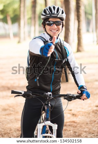 Male Cyclist Showing Thumb Up Sign; Outdoors - stock photo