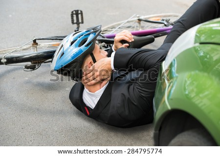 Male Cyclist With Neck Pain Lying On Street After Road Accident - stock photo