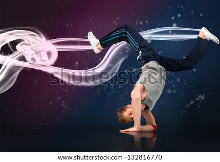 Male dancer balancing on his forearms with white and pink smoke on dark background