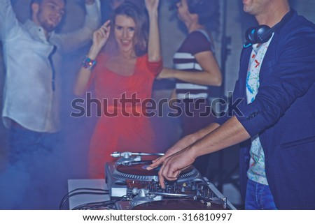 Male deejay adjusting sound on background of dancing friends