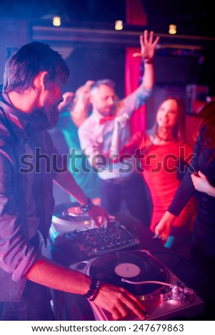 Male deejay adjusting sound with group of dancing friends near by