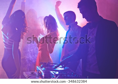 Male deejay and dancing friends enjoying night party