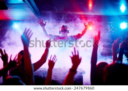 Male deejay in headphones and sunglasses looking at dancing crowd - stock photo