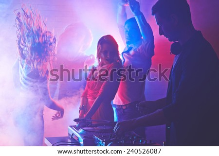 Male deejay mixing sounds with energetic girls and guy dancing on background