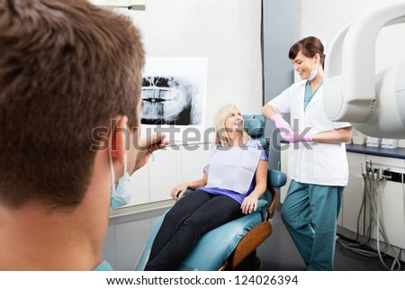 Male dentist examining x-ray image with female assistant communicating with patient at clinic - stock photo