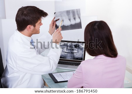 Male dentist explaining dental Xray to female patient in clinic - stock photo