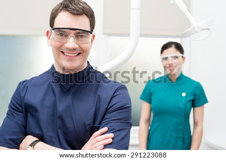 Male dentist with his assistant behind at dental clinic - stock photo