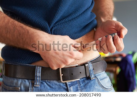 Male Diabetic Injecting Themselves With Insulin - stock photo