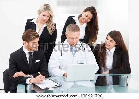 Male doctor and businesspeople using laptop together at desk in office - stock photo