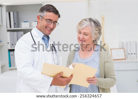 Male doctor and female patient discussing over reports in clinic