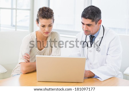 Male doctor and patient using laptop at desk in medical office