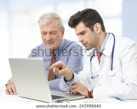 Male doctor and senior patient analyzing the result of the test at computer while they sitting at the nursing home.  - stock photo