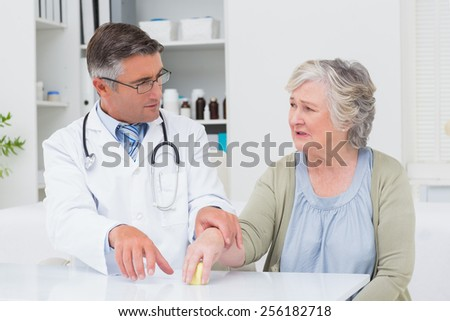 Male doctor assisting female patient to hold weight at table in clinic - stock photo
