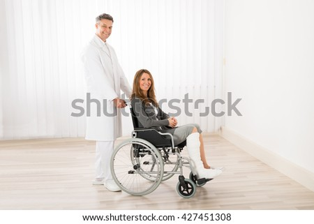 Male Doctor Assisting Happy Woman Sitting On Wheelchair