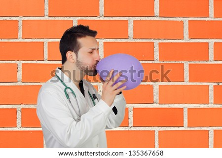 Male Doctor Blowing Air In Balloon Against Wall - stock photo