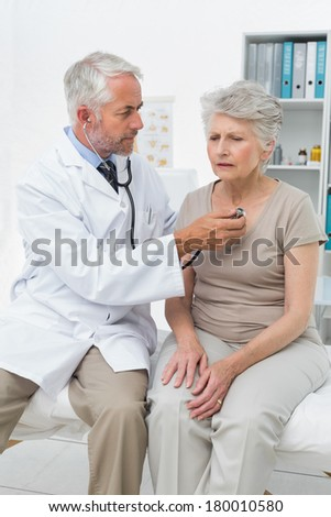 Male doctor checking senior patients heartbeat using stethoscope - stock photo