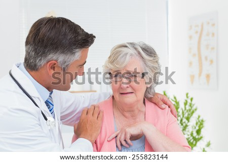 Male doctor consoling senior female patient in clinic - stock photo