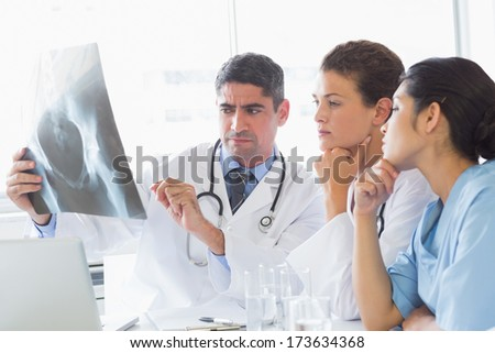 Male doctor discussing xray with colleagues in hospital - stock photo