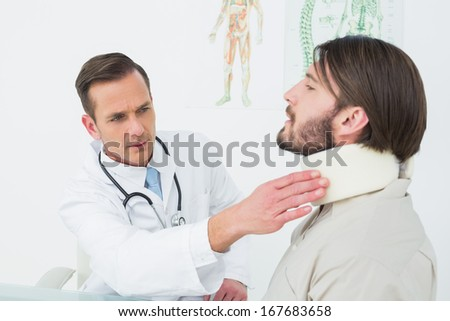 Male doctor examining a patient's neck in the medical office