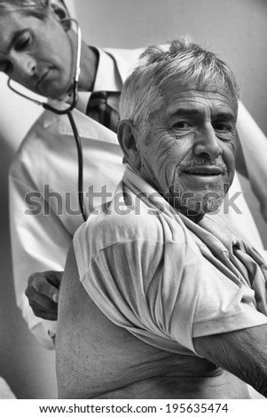 Male doctor examining elder patient at the hospital. - stock photo