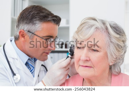 Male doctor examining female patients ear with otoscope in clinic - stock photo