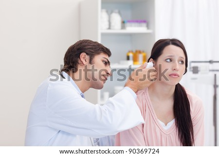 Male doctor examining his female patients ear