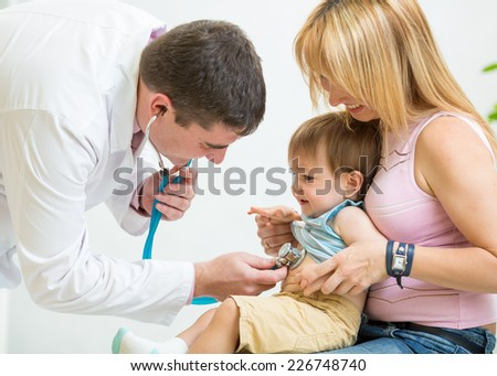 male doctor examining kid boy patient with stethoscope - stock photo