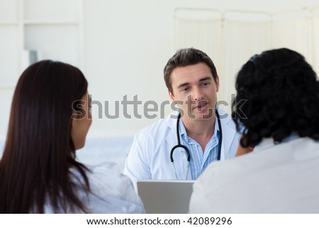 Male doctor explaining diagnosis to a couple during a visit - stock photo