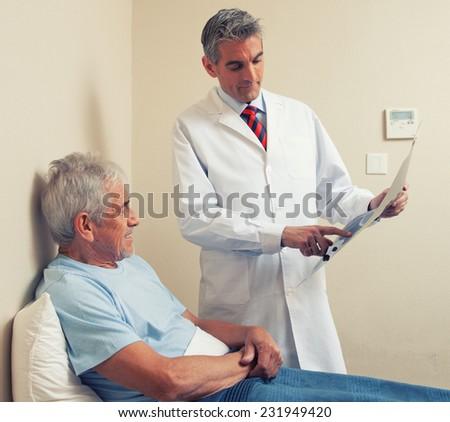 Male doctor explaining medical test to happy elder patient. - stock photo