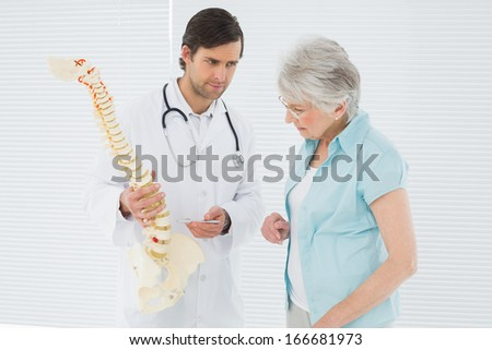 Male doctor explaining the spine to a senior patient in medical office