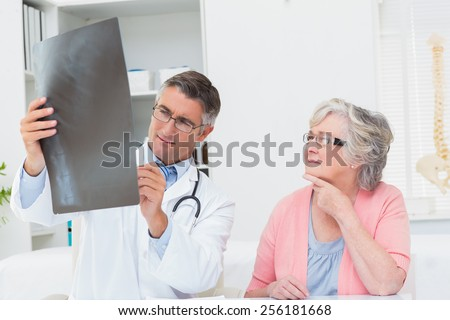 Male doctor explaining x-ray to female patient in clinic - stock photo