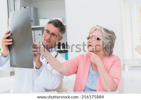 Male doctor explaining x-ray to senior patient in clinic - stock photo
