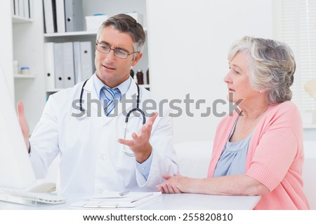 Male doctor explaning reports to senior patient on computer in clinic - stock photo