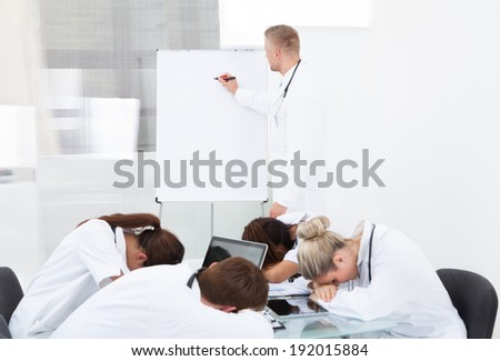 Male doctor giving presentation to tired colleagues sleeping at desk in clinic - stock photo