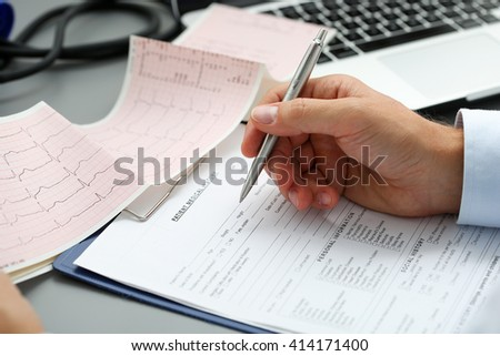Male doctor hands with cardiogram chart on clipboard pad fill medical history with silver pen. Cardio therapeutist assistance, physician make cardiac physical, pulse measure document, arrhythmia idea - stock photo