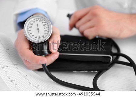 Male doctor hands with sphygmomanometer and cardiogram lying on table, close up view