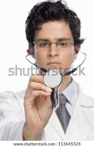 Male doctor holding a stethoscope - stock photo