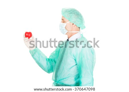 Male doctor holding heart model - stock photo