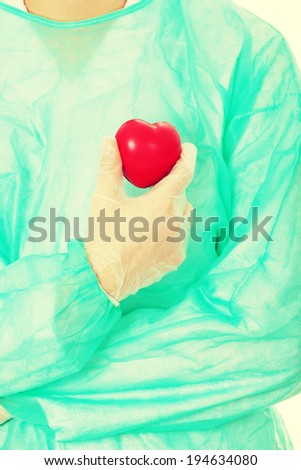 Male doctor holding heart shape toy - stock photo
