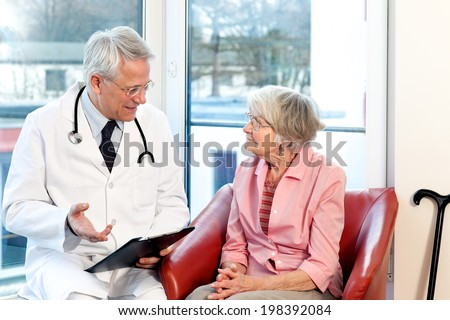 Male doctor in consultation with a senior female patient sitting having a discussion and offering a detailed explanation as they chat in front of a window in the hospital - stock photo