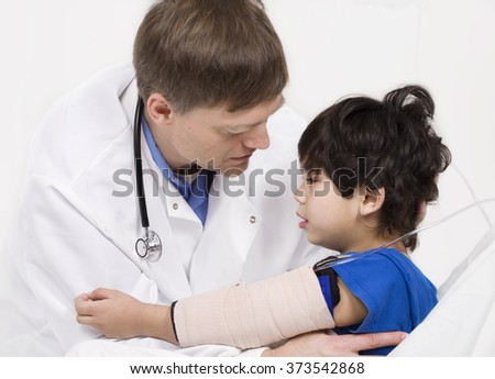 Male doctor in early forties comforting five year old disabled patient during office visit - stock photo